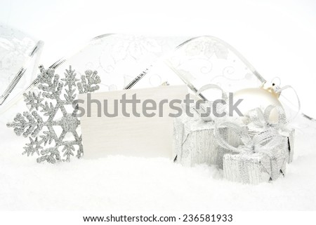 Decoration of silver christmas baubles and gifts with ribbon with wishes card on snow white background - stock photo