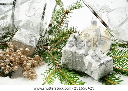 Decoration of silver christmas gifts, silver ribbon on snow christmas tree branch on white - stock photo