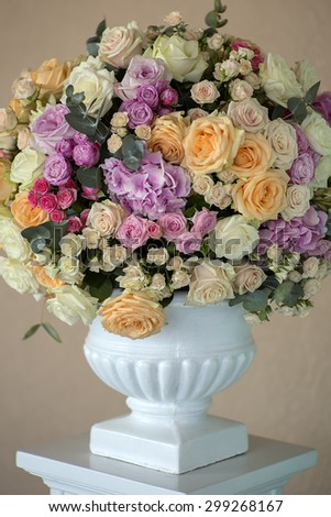 Decoration of wedding bouquet of fresh beautiful flowers of roses and peony white pink violet purple yellow lilac and orange colours in big vase on beige background, vertical picture - stock photo