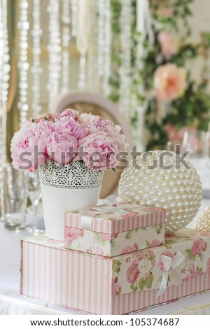 decoration of wedding table. flowers in vase with gift boxes that stand on each other and ball - stock photo