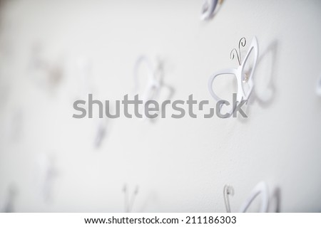 decorations in the shape of butterfly on white wall - stock photo