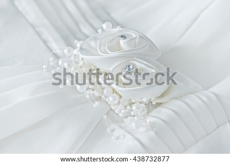 Decorations of white wedding dress closeup - stock photo