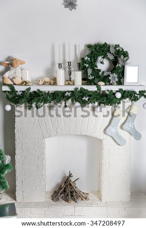Decorations on the Christmas fireplace in the form of candlesticks, Christmas wreath and photo frames, socks for Christmas gifts - stock photo