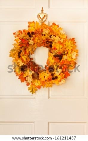Decorative autumn wreath hanging on front door - stock photo