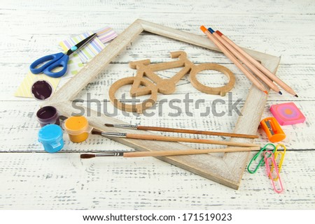 Decorative bicycle with needlework composition on wooden background - stock photo