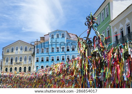 Decorative Brazilian wish ribbons tied to a church gate frame a view of bright colonial architecture of Pelourinho Salvador Bahia Brazil - stock photo