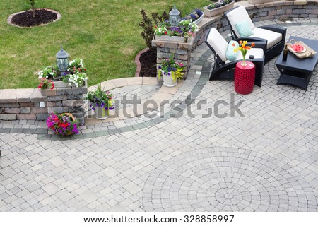 Decorative brick paving on an outdoor patio with a circular pattern and curved steps flanked by spring flowers leading to a green lawn, comfortable seating in the background - stock photo