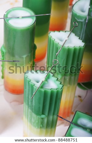 Decorative candle making using colorful wax at a professional chandler - stock photo