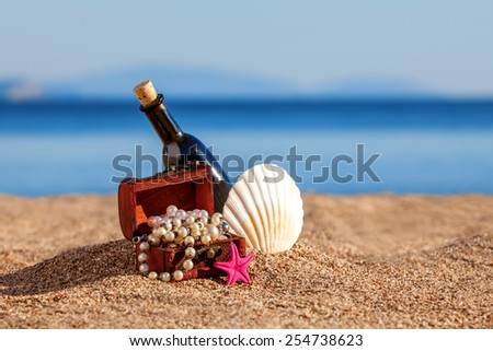 Decorative chest with jewelry,bottle and starfish on a beach - stock photo