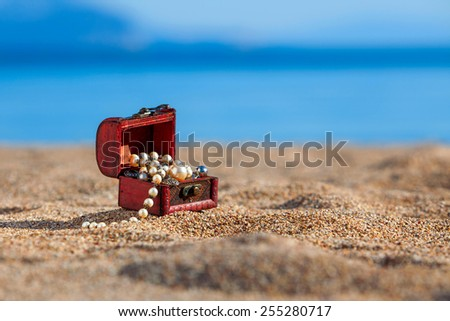 Decorative chest with jewelry  on a beach - stock photo