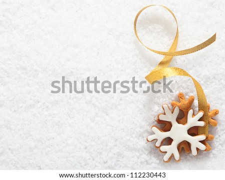 Decorative Christmas biscuit ornament in the form of an iced snowflake with a twirled gold ribbon lying on a bed of fresh white snow with copyspace for your text - stock photo