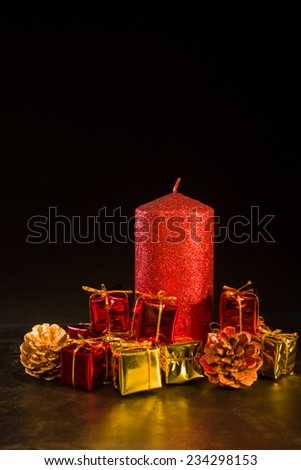 Decorative christmas composition, with a red candle, pines and gifts - stock photo
