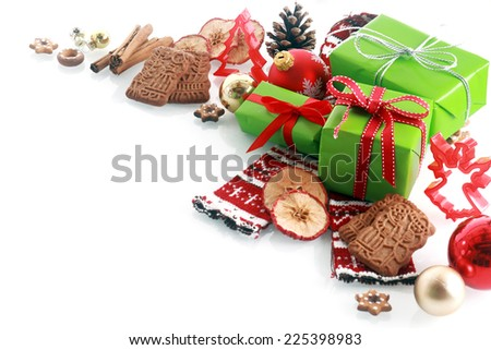 Decorative Christmas corner decoration over white with copyspace with red and green gifts, speculoos biscuits, spices, ornaments and cookie cutters - stock photo