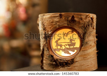 Decorative Christmas tea light depicting Santa on a reindeer sleigh at a Christmas Market - stock photo