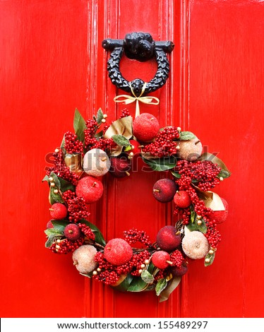 decorative Christmas wreath tied to knocker on red door - stock photo