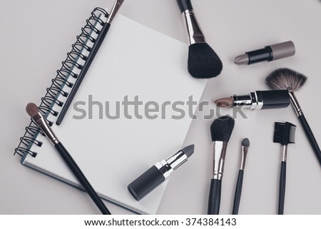 decorative cosmetics with notebook on green background - stock photo
