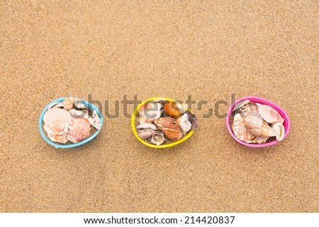 Decorative Easter egg baskets on the beach filled with seashells for use as a background. Room for copy left along the top half of the image. - stock photo