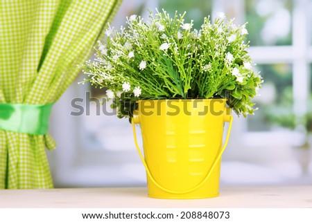 Decorative flowers in pot on windowsill - stock photo