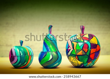 Decorative fruit - pears and apples, made of wood and painted by hand paints. modern art - stock photo