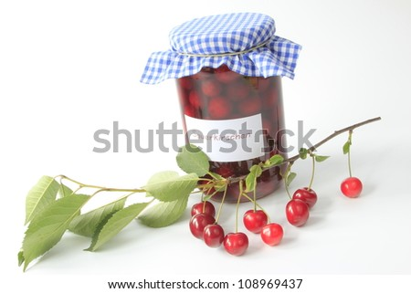 decorative glass with boiled sour cherries with a twig with ripe fruits - stock photo