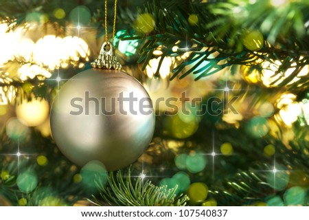 Decorative gold bauble in a Christmas tree in front of a glitter background - stock photo