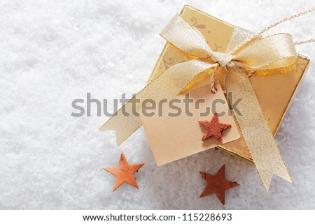Decorative gold Christmas gift in winter snow with a blank label for your seasonal greeting and a scattering of small stars - stock photo