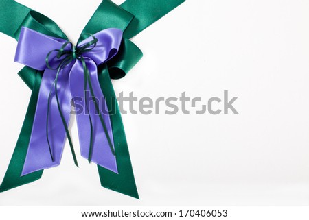 Decorative green and blue bow made from two overlaid ribbons on a white background with copyspace for your greeting or best wishes for a festive or special occasion - stock photo