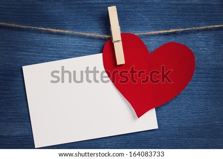 decorative hearts hanging on the rope against blue wood wall, valentine theme - stock photo
