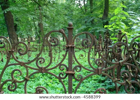 decorative iron fence of a grave - stock photo