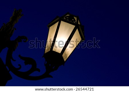 Decorative lamp post photographed in the clear dark blue midnight - stock photo