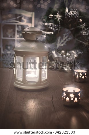 Decorative lantern, candles and Christmas decorations on wood. Greeting card with space for your text in the left bottom corner of the image. - stock photo