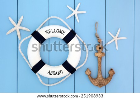 Decorative lifebuoy, anchor and starfish sea shells over wooden blue background. - stock photo