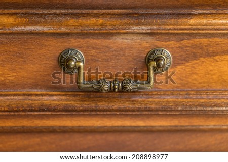 Decorative metal ornate drawer handle on a wooden cupboard  - stock photo