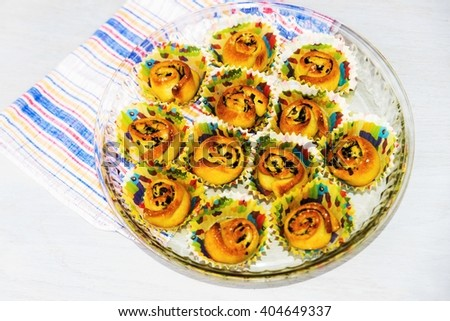 Decorative mini scroll from pizza dough with cheese, garlic and herb leaf, good pie for snack or appetizer, on plate with colorful mini basket, cloth on white background - stock photo