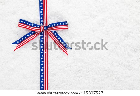 Decorative patriotic American ribbon and bow with the stars and stripes on winter snow for your Christmas greeting - stock photo