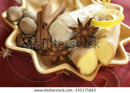 Decorative plate with ginger, lemon peel, anise, clove, nutmeg and cinnamon sticks. - stock photo