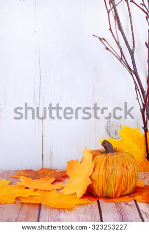 Decorative pumpkin, fall leaves and bare branches on wood table in front of whitewashed rustic wooden background. Gold, yellow and orange colors. Copy space on left. Good for fall or Halloween. - stock photo