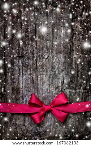 Decorative red ribbon and bow over wooden background/ Christmas background with copyspace - stock photo