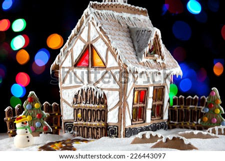 Decorative snowman and gingerbread house with light inside on blurred lights background. Rural Christmas night scene - stock photo