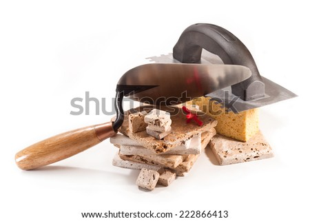 Decorative tiles, trowel and spatula on a white background - stock photo