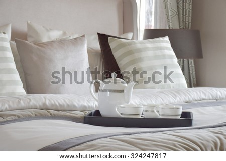 Decorative tray of tea set on the bed in modern bedroom interior - stock photo