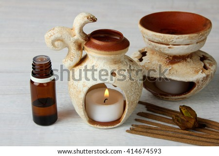 decorative vases with a candle and a jar with essential oils with the incense on white wooden background - stock photo