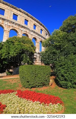 Decorative vegetation and distant ruins of an ancient Roman Amphitheater, Pula, Croatia - stock photo