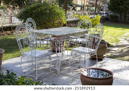 Decorative vintage metal white table and chairs furniture in a garden - stock photo