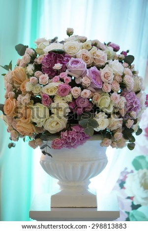 Decorative wedding bouquet of fresh beautiful flowers of roses and peony white pink violet purple yellow lilac and orange colours in big vase on blue curtain background, vertical picture - stock photo