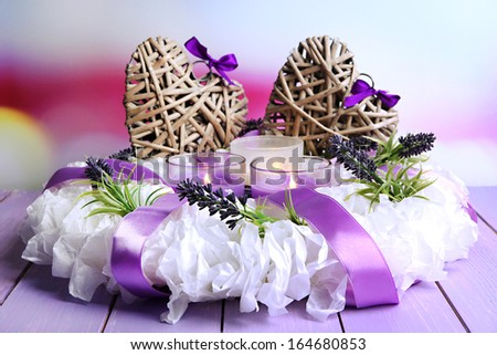 Decorative wreath with candles and wicker heats on table on bright background - stock photo
