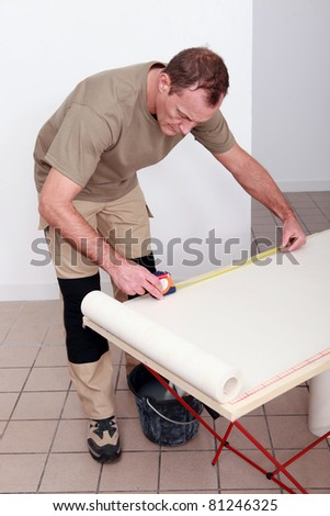 Decorator measuring a roll of wallpaper - stock photo