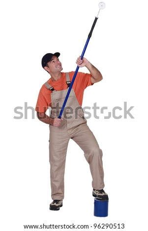 Decorator painting a ceiling with a roller - stock photo