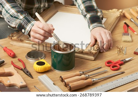 Decorator varnishing a wooden frame hands close up with DIY tools, hobby and craft concept - stock photo
