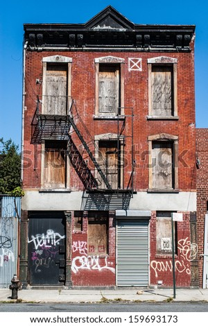 Decrepit old house with red bricks and graffiti in Queens (New York) - stock photo